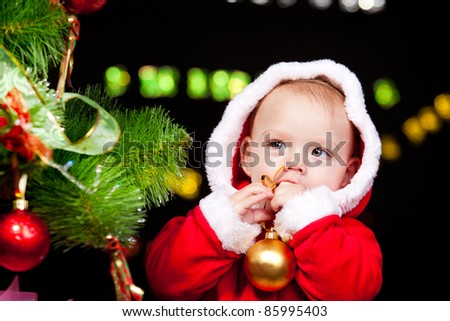 Portrait of a sweet baby boy beside Christmas tree - stock photo