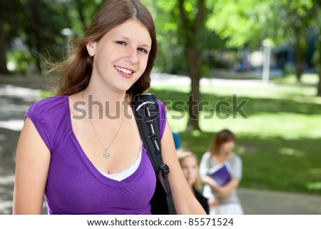 Portrait of a sweet college girl smiling with friends in background - stock photo