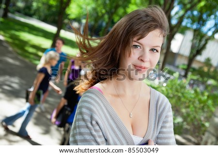 Portrait of a sweet college girl with friends in background - stock photo