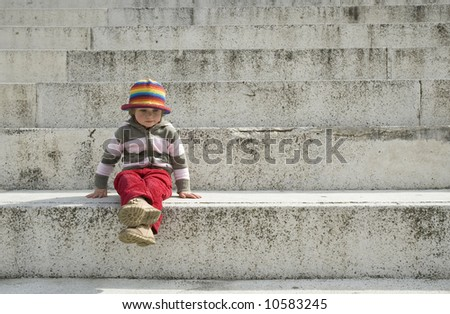 portrait of a sweet girl sitting on the steps - stock photo