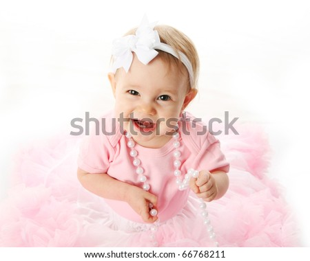 Portrait of a sweet infant wearing a pink tutu, necklace, and headband bow, isolated on white in studio - stock photo
