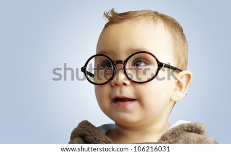 portrait of a sweet kid wearing round glasses over a blue background - stock photo