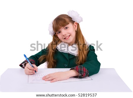 Portrait of a sweet little girl at her classroom, writing an exam. A happy schoolgirl doing her homework. Young student writing. - stock photo
