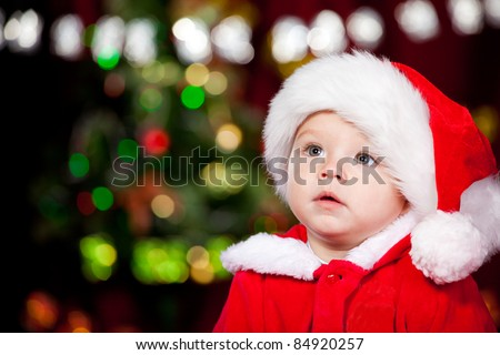 Portrait of a sweet toddler in Santa hat - stock photo