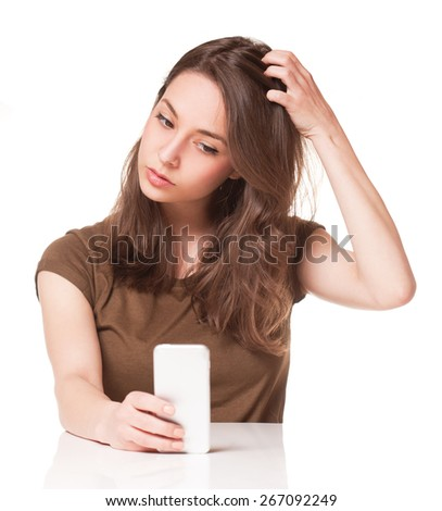 Portrait of a sweet young brunette using mobile phone. - stock photo