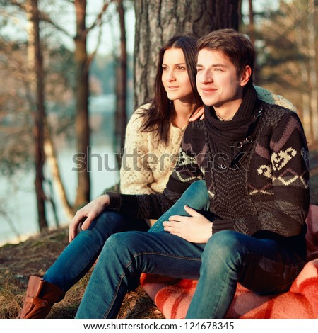 Portrait of a sweet young couple in love sitting together outdoors in forest - stock photo