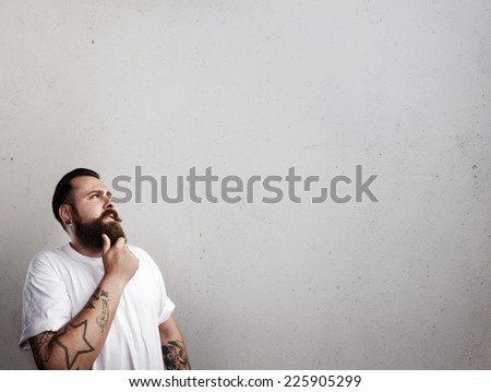 Portrait of a tattooed bearded man thinking