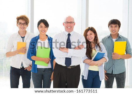 Portrait of a teacher and his students in a row  - stock photo