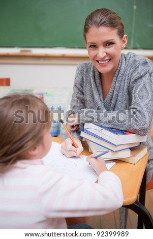 Portrait of a teacher explaining something to her pupil in a classroom - stock photo