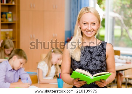 Portrait of a teacher on a background of pupils - stock photo