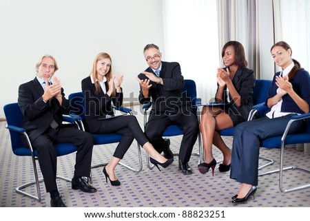 Portrait of a team of happy successful businesspeople sitting together smiling and celebrating at the office - stock photo