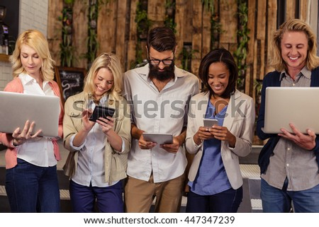 Portrait of a team of hipsters with multimedia tools in the office - stock photo
