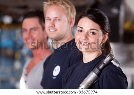Portrait of a team of mechanics with a woman in the forground - stock photo