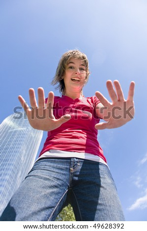 Portrait of a teen girl in casual clothing taken from a low angle with a modern building, trees and a blue sky in the background - stock photo