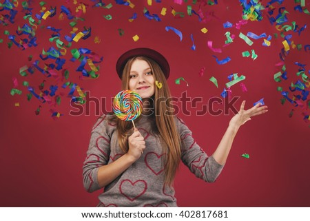 Portrait of a teen girl throws up a multi-colored tinsel and confetti. beautiful girl wearing hat holding big striped lollipop