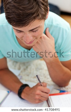 Portrait of a teen guy studying on the floor with his friends - stock photo