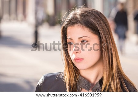 portrait of a teen sad girl closeup, outdoor city street - stock photo