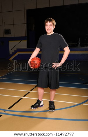 Portrait of a Teenage Basketball Player in Gym - stock photo