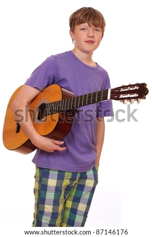 Portrait of a teenage boy holding a classical guitar - stock photo