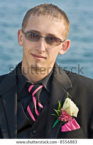 Portrait of a teenage boy in a tuxedo. Background is a blue ocean. The teen is dressed for a high school prom but the photo could be used to represent any formal occasion. - stock photo