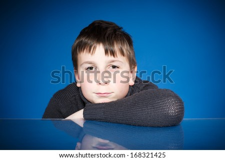 Portrait of a teenage boy on a blue background - stock photo