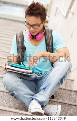 Portrait of a teenage boy sitting with digital tablet on steps - stock photo
