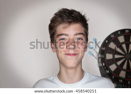 portrait of a teenage boy with dartboard in background - stock photo