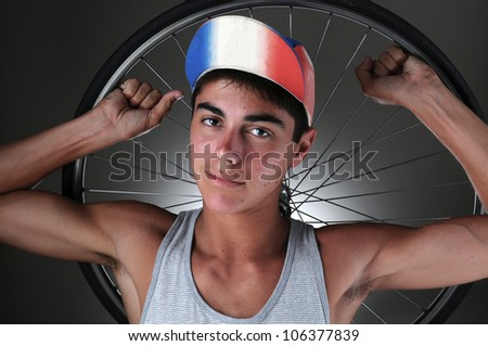 Portrait of a teenage cyclist holding a wheel behind his head. Closeup in horizontal format with a gray light ot dark background. - stock photo