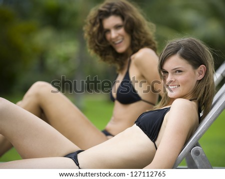 Portrait of a teenage girl and her mother reclining on lounge chairs