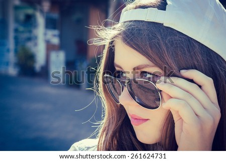 Portrait of a teenage girl in a baseball cap and sunglasses - stock photo