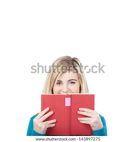Portrait of a teenage girl looking over book against white background - stock photo