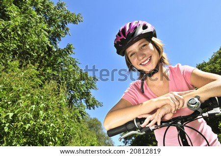 Portrait of a teenage girl on a bicycle in summer park outdoors - stock photo