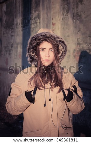 Portrait of a teenage girl outdoor wearing winter coat with the faux - fur hood on. Toned effect