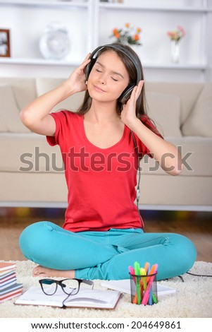 Portrait of a teenage girl sitting on floor at home listening to music in headphones - stock photo