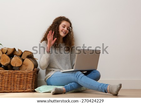 Portrait of a teenage girl using laptop and waving hello on chat - stock photo