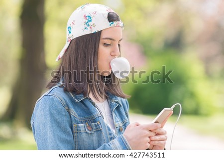 Portrait of a teenage girl using phone and listening to music on her headphones. She is wearing denim jacket and a baseball cap and blowing a bubble of chewing gum - stock photo