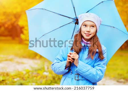 Portrait of a teenage girl walking in the park on a background of yellow autumn leaves - stock photo