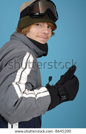 Portrait of a teenage snowboarder giving thumbs up