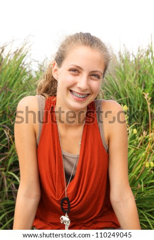Portrait of a teenager a huge smile wearing an orange shirt