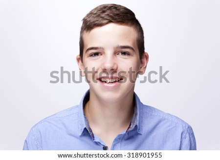 Portrait of a teenager boy smiling on gray background - stock photo