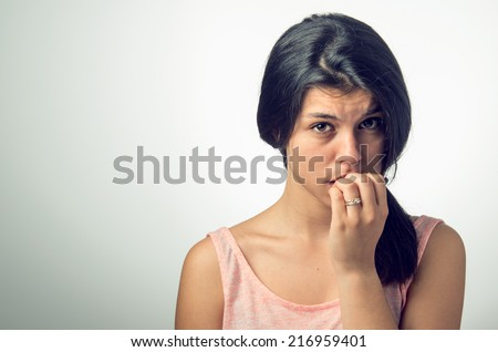 Portrait of a teenager brunette girl with nervous expression and nail-biting - stock photo