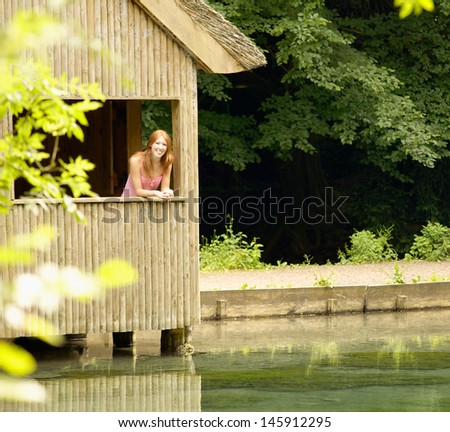 Portrait of a teenager girl leaning on the window of a wooden hut structure on a lake during a summer vacation in the forest, smiling and relaxing.