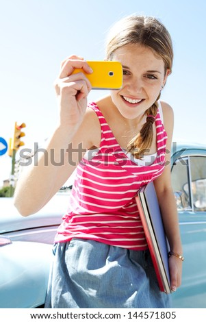 Portrait of a teenager girl using with her smartphone to take photos while leaning on a classic car in the city during a sunny day with a blue sky, smiling. - stock photo