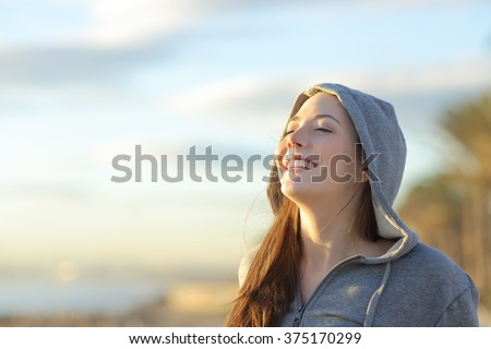 Portrait of a teenager girl wearing hood breathing deep fresh air on the beach at sunrise in a summer sunny day with a beautiful warm sky in the background - stock photo
