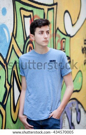 Portrait of a teenager rebellious man on a wall with graffiti background - stock photo