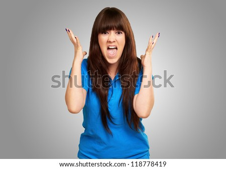 portrait of a teenager screaming and angry on gray background - stock photo