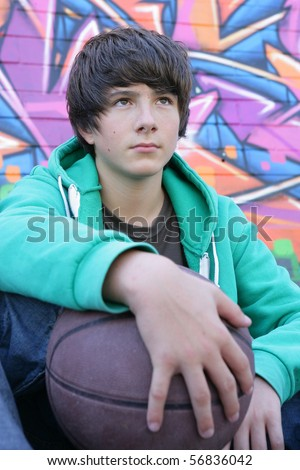 Portrait of a teenager sitting in front of a wall of graffiti with a basketball - stock photo