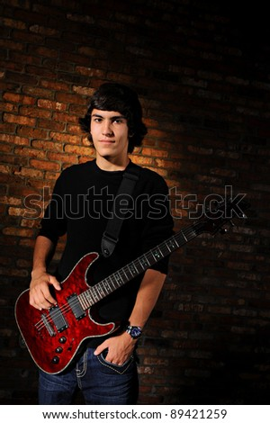 Portrait of a teenager with one hand in his pocket and the other on his red guitar.  Studio shot. - stock photo
