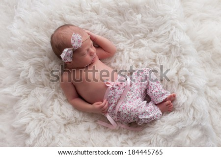 Portrait of a ten day old sleeping newborn girl wearing white and pink floral pants with a matching headband. She is sleeping on a white Flokati (sheepskin) rug.