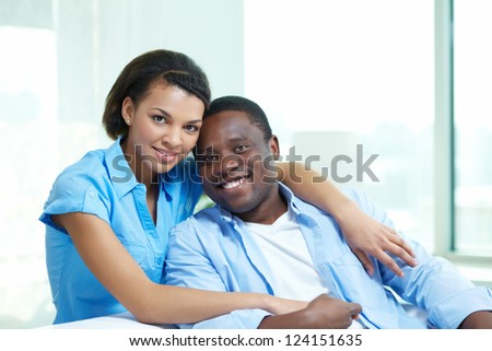 Portrait of a tender African-American couple cuddling at home - stock photo